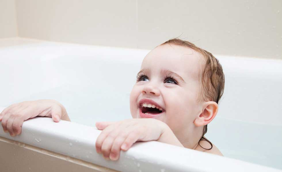 baby in bath smiling