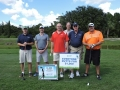 Tom Stephen, Keith Swan, Bo Andsersson, and Matt Servant putt for $10,000 as officials Mills and Mest looks on