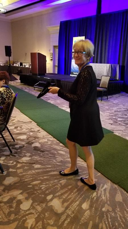 Program-Director-Margaret-Martens-showing-auction-items